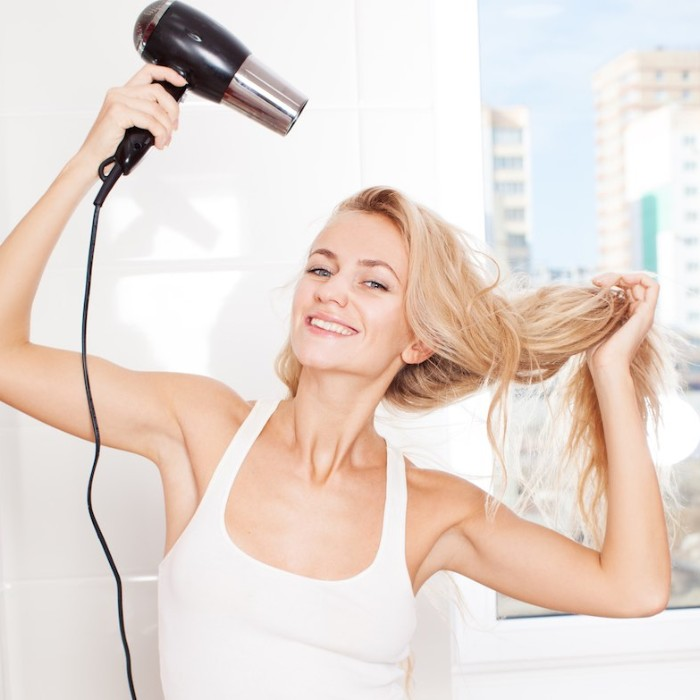 Woman dry hair hairdryer at bathroom. Female with dryer at home